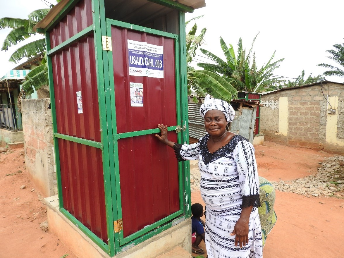 Dorcas proudly stands outside her constructed toilet