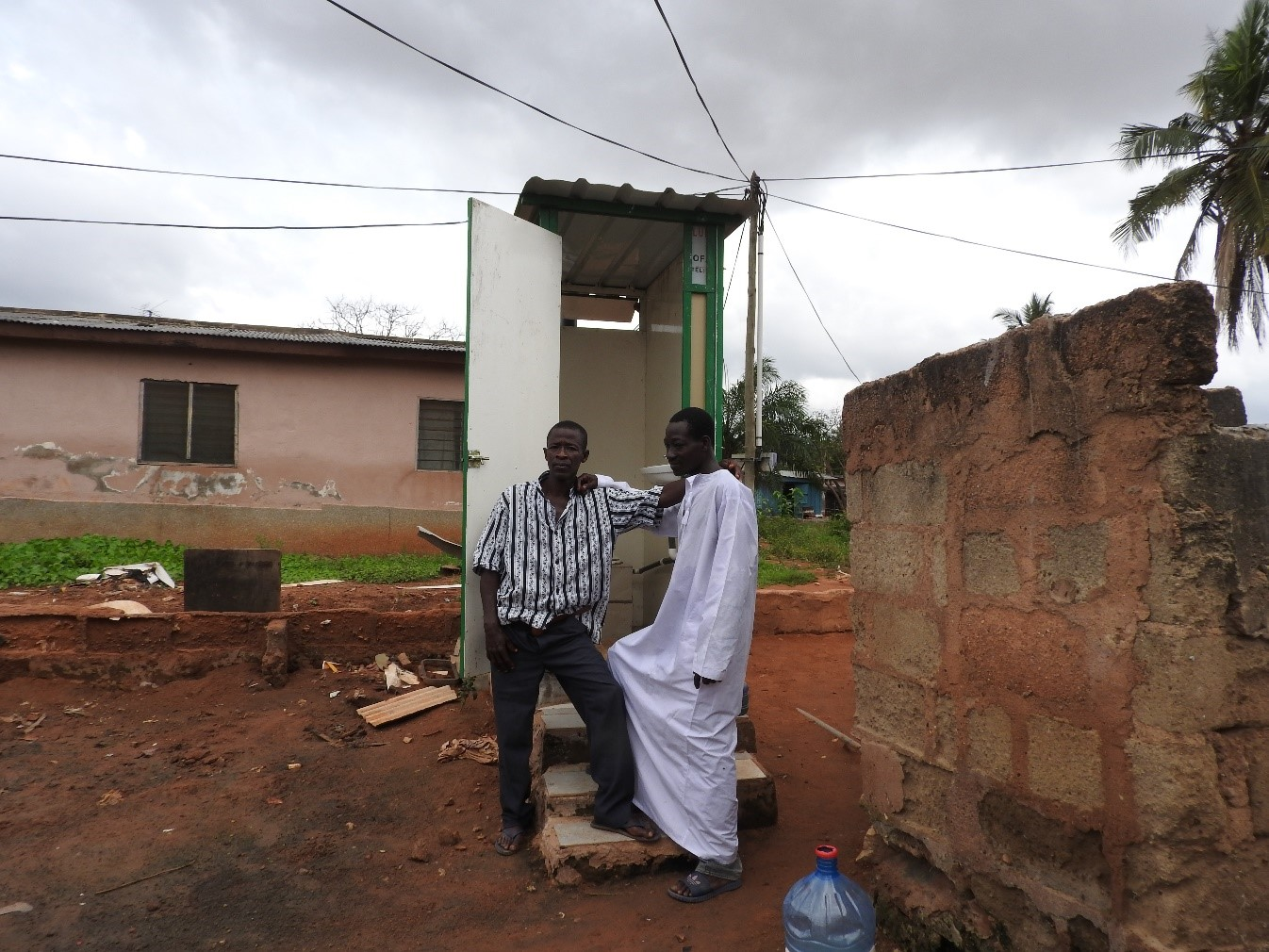 iliasu and issaka stand together outside their 2 month old biofil toilet in anyaa just